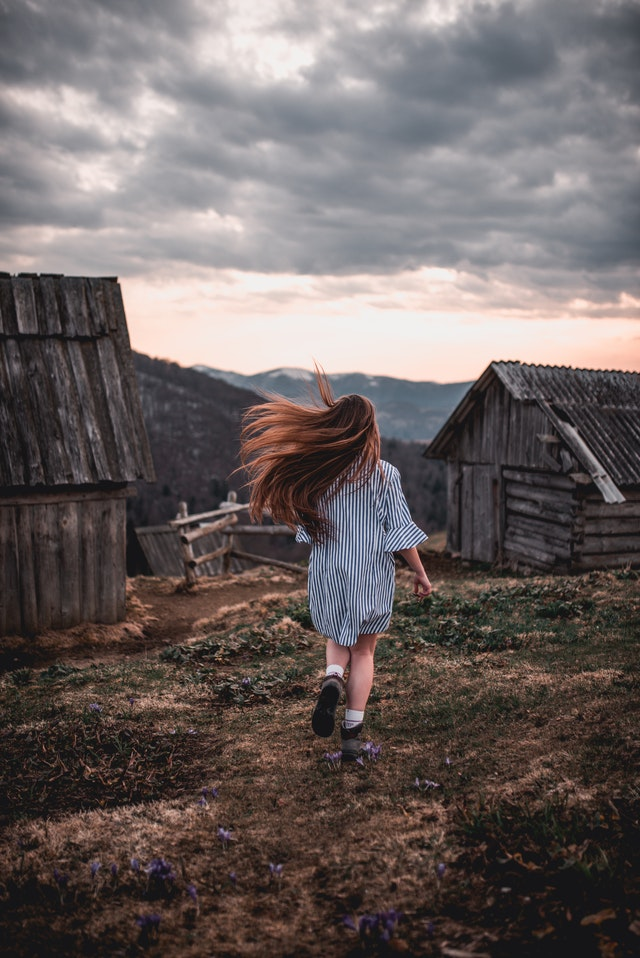 This image illustrates the feelings, joy, and my life as a farmer's daughter. This is a photo of a young girl running across a field towards some nearby barns. Her long hair is blowing in the wind.