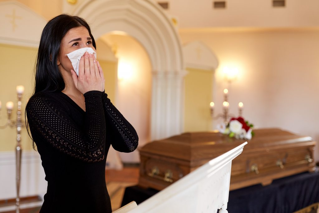 This is an image of a grieving woman in a crisis. She is in a church like setting near a casket.