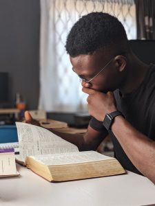 This is a photo of a young man reading the bible.  You will find help for times of trouble in the Bible. It tells you how good and powerful God is and what he promises to do for his children.